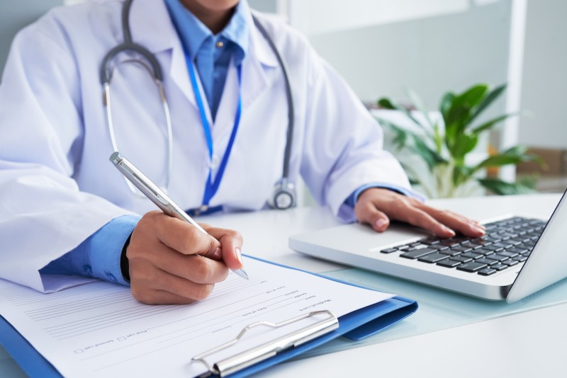 Doctor checking information in computer program before filling medical card